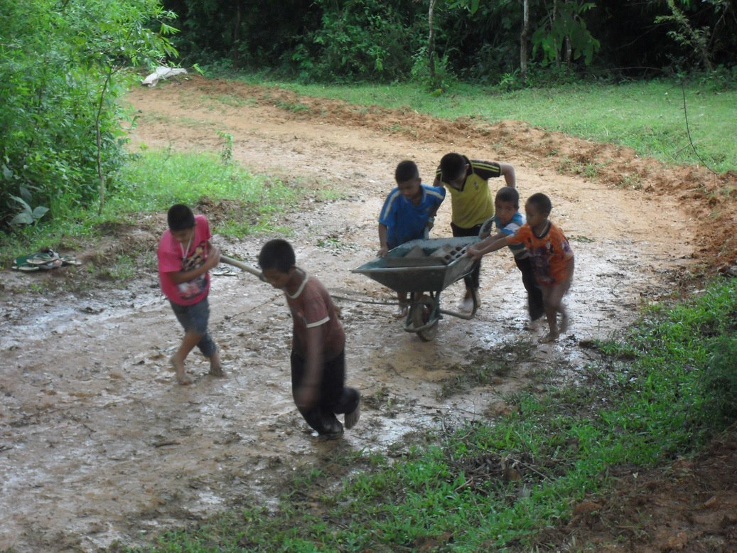 Children are helping one another in carrying the construction materials for constructing the pagoda of Lao Lew Archanai Temple (branch temple along the border of Thailand-Burma) (photo of activities to make merits in 2012)